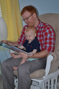 Joe Backe reads to his 9 month old son (and our grandson), Walt.
