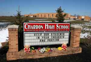 Flowers and gifts sit along the Chardon High School sign along with a message of thought and prayer in Chardon